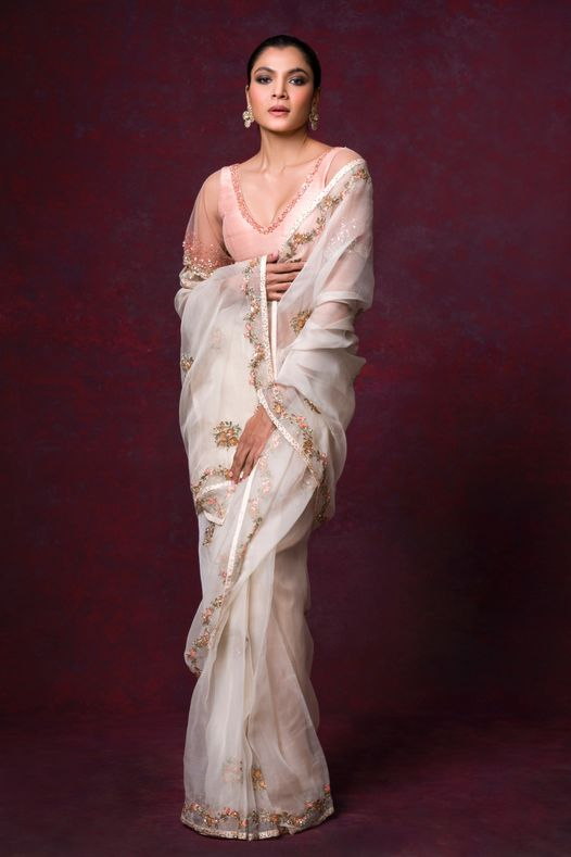 Subtle and sheer ivory organza saree embroidered with zardosi and resham teamed with a delicate bell-sleeved blouse.  Kindly WhatsApp  on +91-9833520520 for more information. 2021-09-21