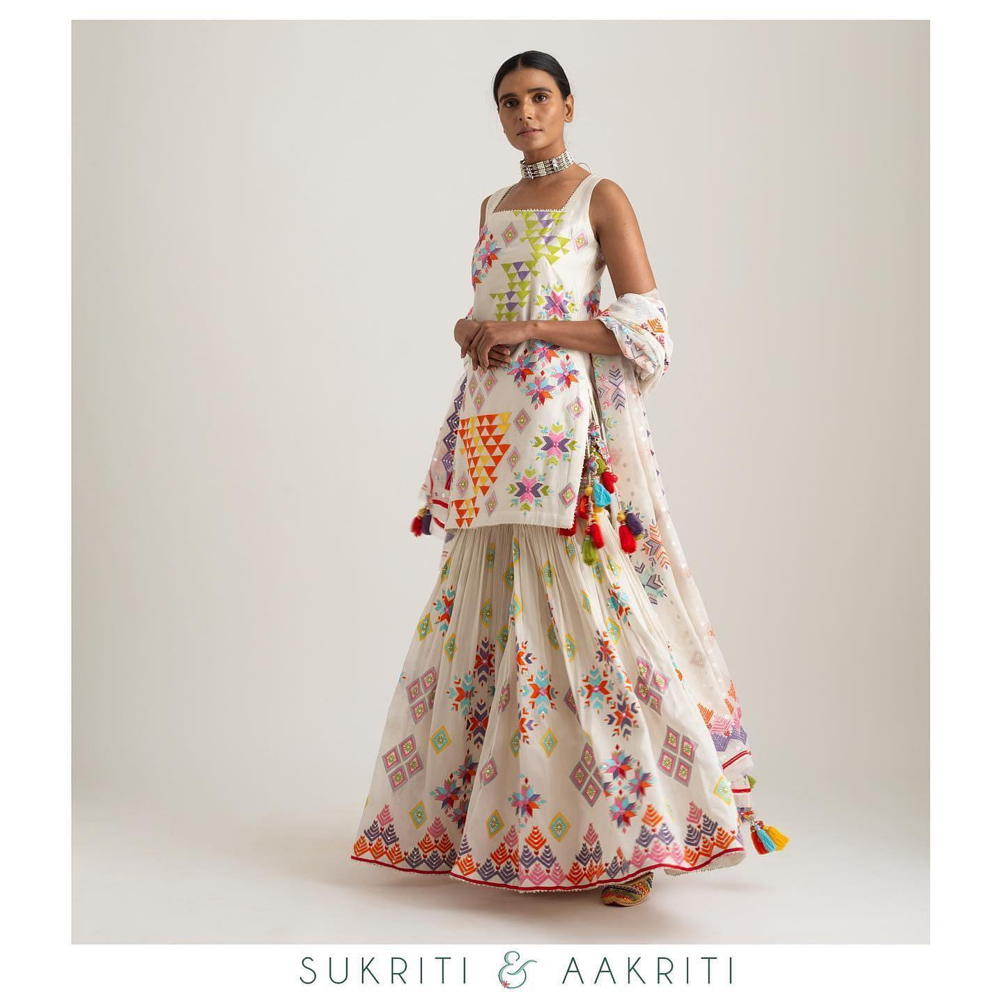 Off white short kurta paired up with printed sharara and tikli with hand embroidered detailed. 2021-09-21