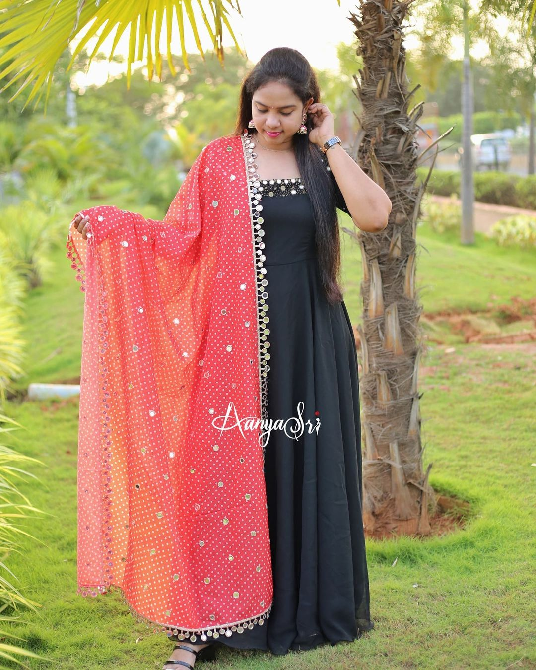 Black long frock with intricate real mirrors work on the yoke and sleeves paired with an elegant mirror worked red(has a slight orange undertone) colored bhandini dupatta. 2021-09-21