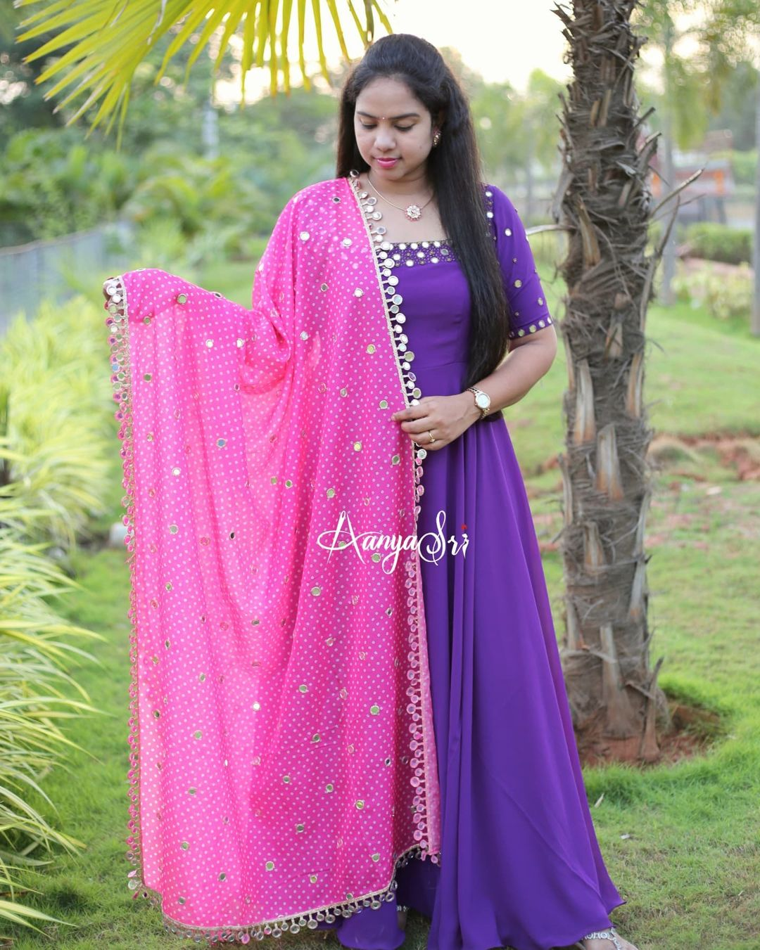 Purple longfrock with intricate real mirrors work on the yoke and sleeves  paired with an elegant mirror worked pink  colored bhandini dupatta. Price : RS. 4850/- 2021-09-21