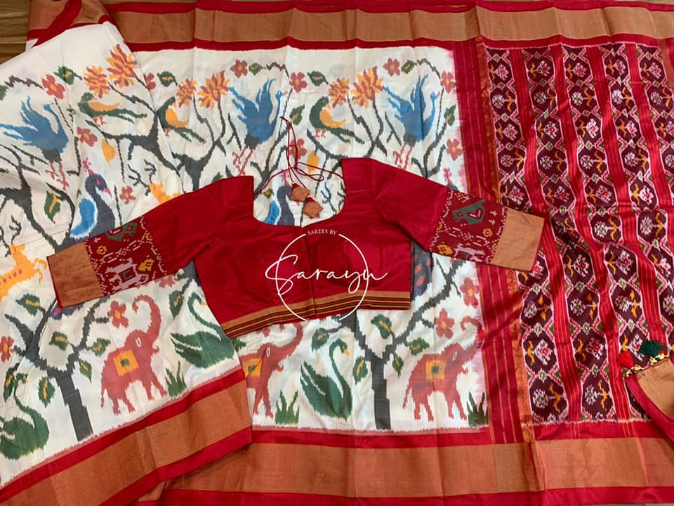 Type: Ikkat Silk. Description:  Beautiful half white very fine double Ikkat ( exclusive design) Silk Saree all over animal design weave with Patola Pallu  complemented with contrast red 3/4 sleeve Pattern blouse. 2021-09-22