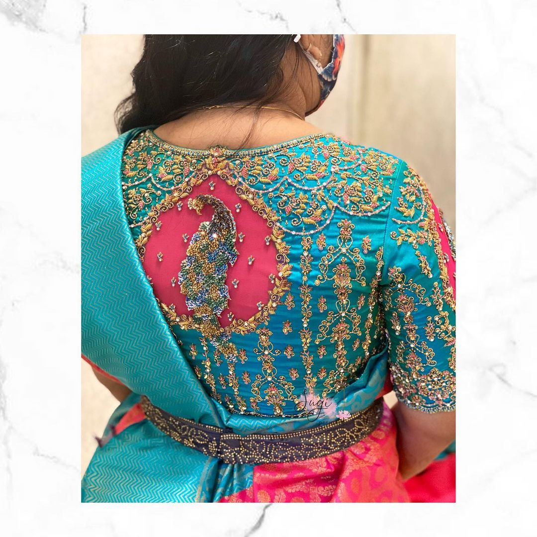 Stunning teal blue and pink color combo bridal blouse with peacock hand embroidery maggam work.  2021-09-22