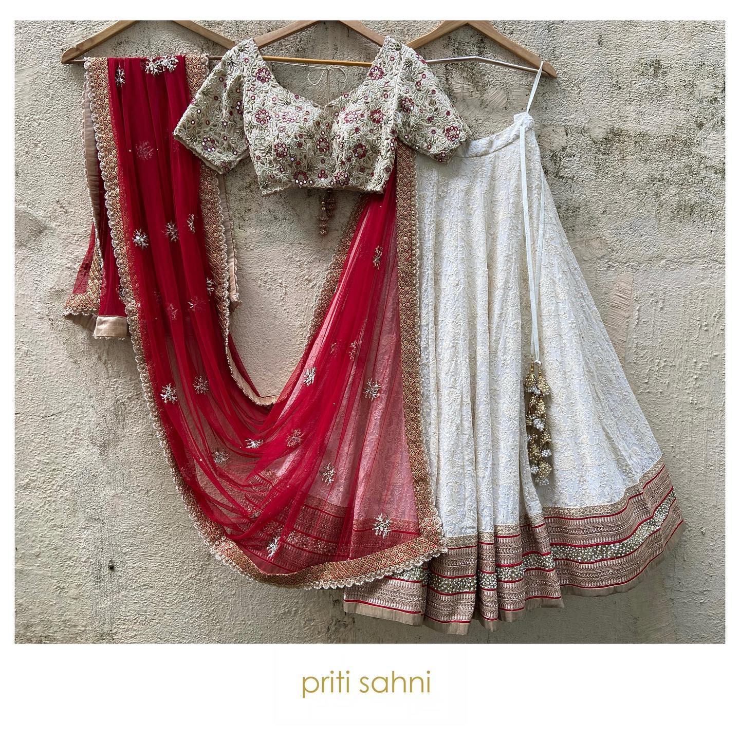 Ivory Edit.  Ivory thread work Lehenga with intricate gots and sequin work border in red accent; delicately hand embroidered raw silk blouse with resham beads zardozi and mirrors paired with butti work dupatta in scalloped edging  To get your dream outfit designed DM or Whatsapp on +91-9022617481. 2021-09-25