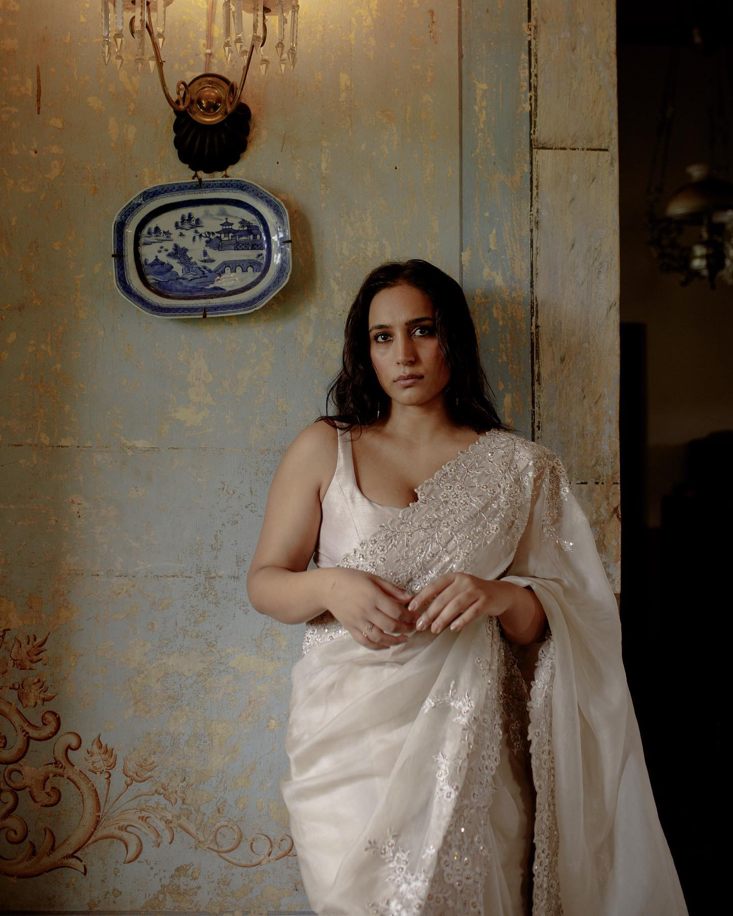 Chitra Nariin Saree reimagined in a dreamy shade of white and enriched by a feminine silhouette with shimmering hand-embroidered details that are inspired by the timeless beauty around us. It is paired with a textured raw silk sleeveless blouse. 2021-09-28