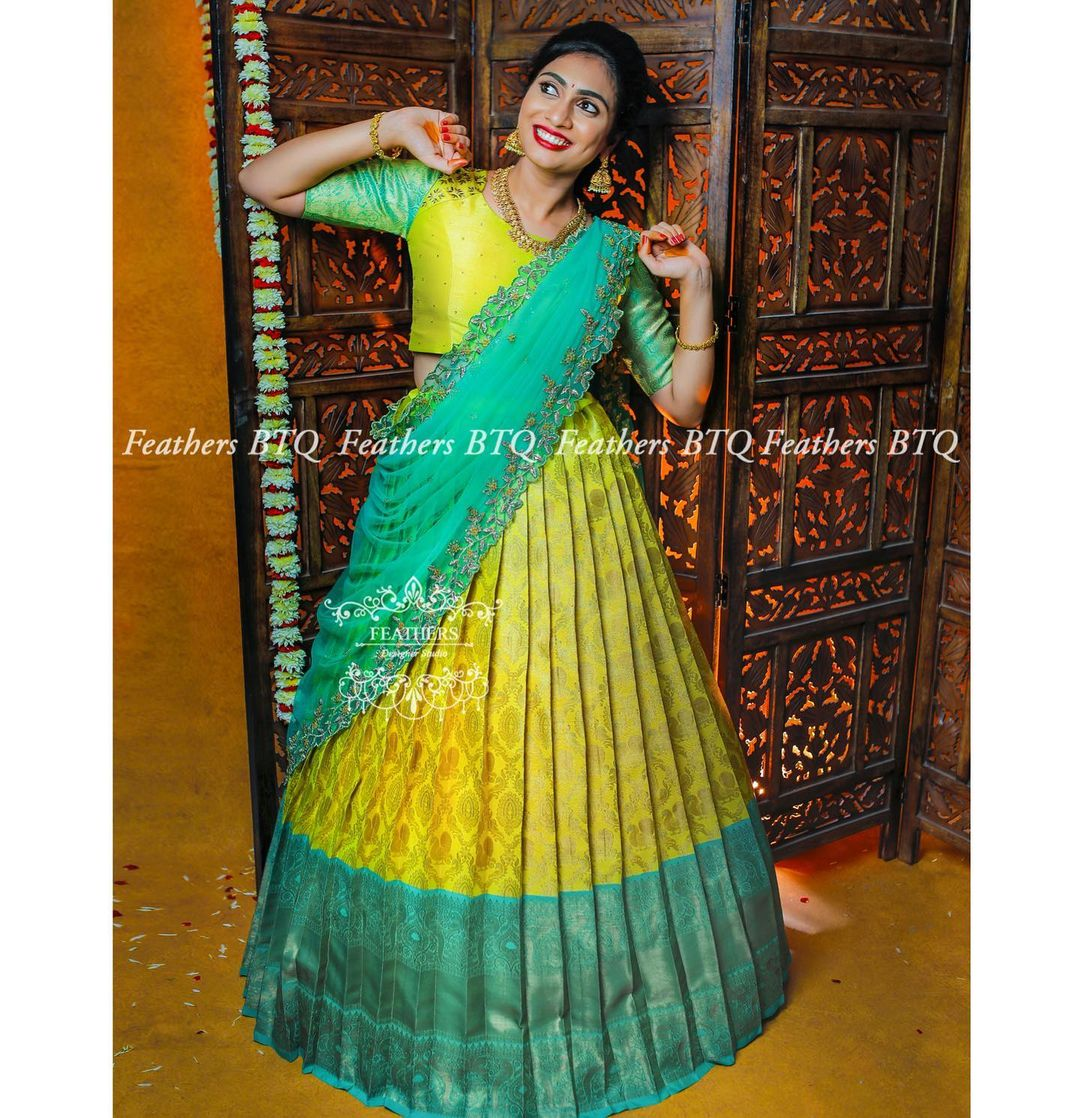 Gorgeous yellow and sea green color combination pattu lehenga and blouse with cutwork dupatta.  2021-09-30