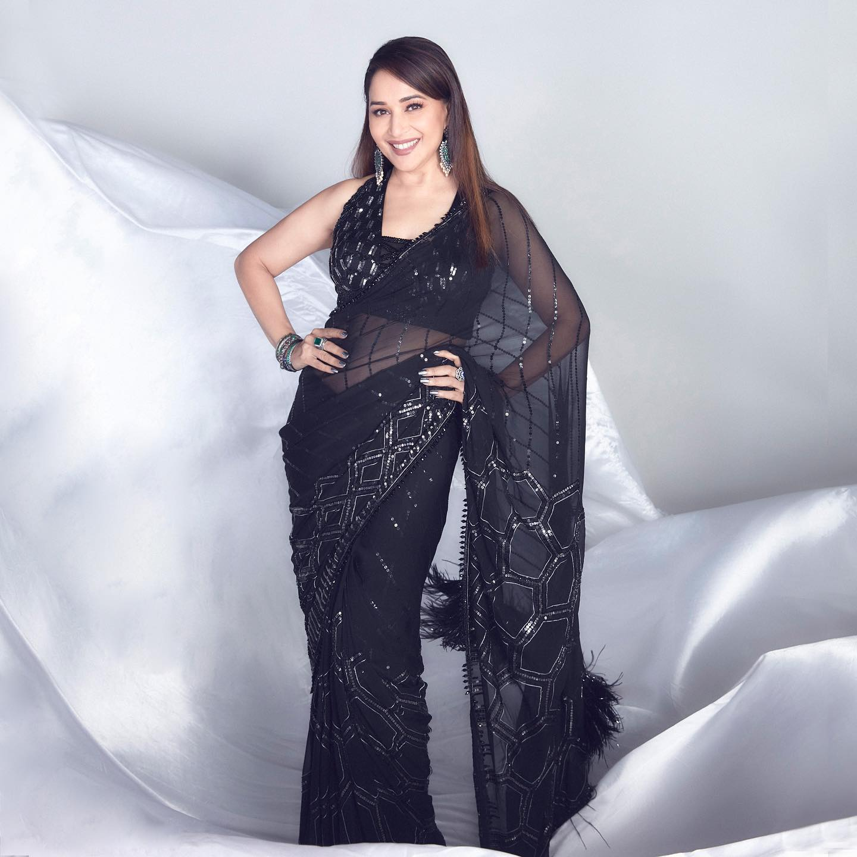 Elegance belongs to Madhuri Dixit Nene beautifully wrapped in six yards of a starry ebony sky. Outfit: Manish malhotra. 2021-10-03