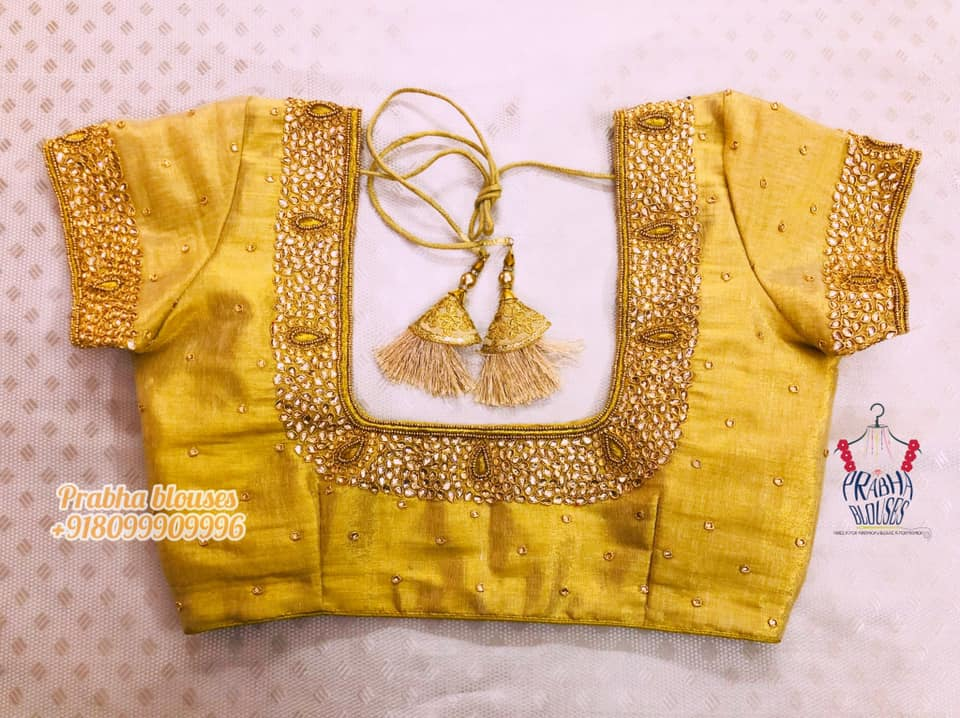 Gorgeous yellow color bridal blouse with bead and kundan maggam work on neckline and sleeves. 2021-10-13