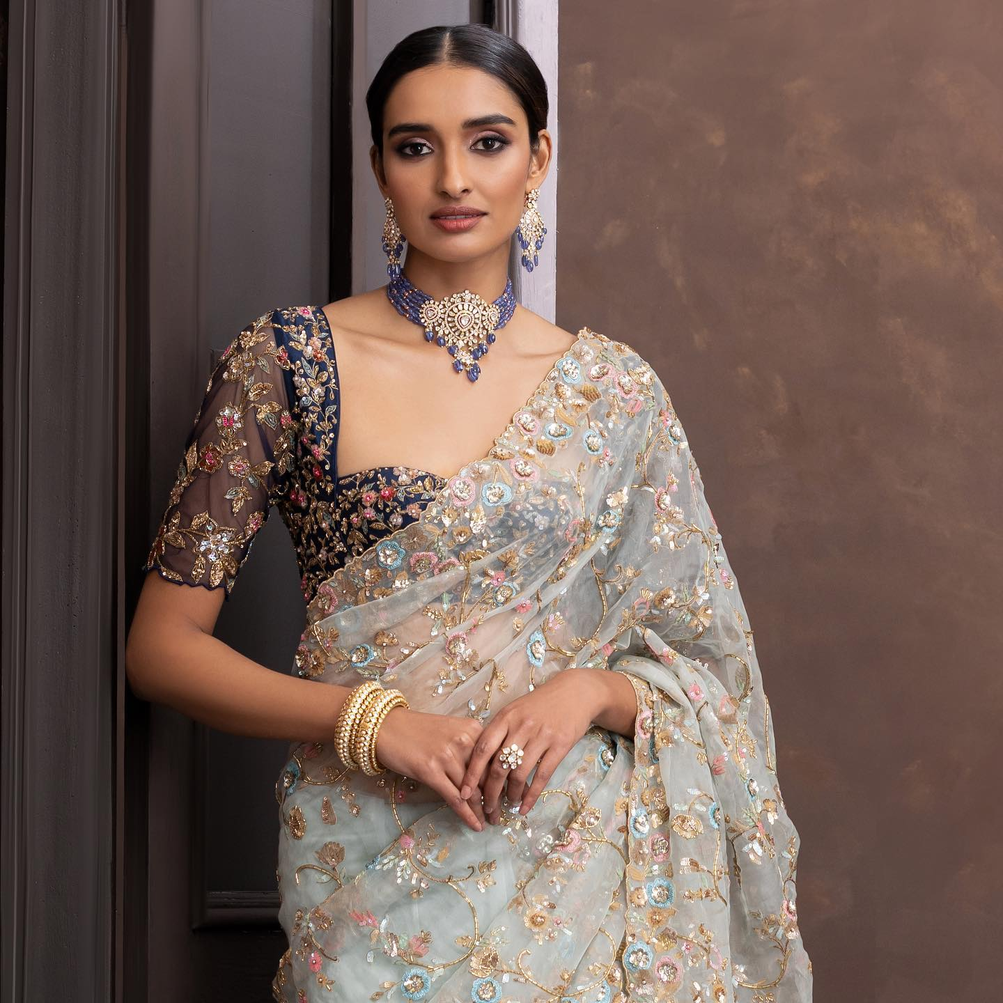 Gorgeous ice blue color organza saree and purple blouse with classy hand embroidery work.  2021-10-15