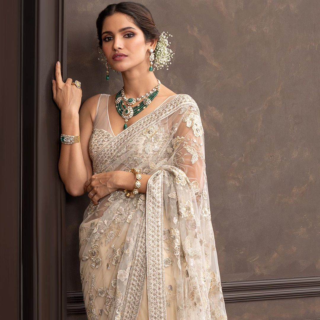 A classic ivory net saree with tonal floral embroidery. . Wedding Couture 21-22 Shyamal & Bhumika . 2021-10-18