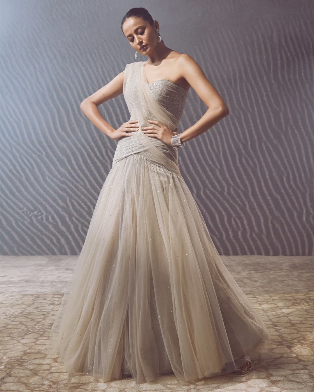 Sonali is seen here wearing foil crinkle and tulle draped grown in the oyster shade. The one shoulder bodice features fluting  and is embellished with crystals all over. The attached jersey and tulle stole extends from the shoulder in the back and can be accessorized with a wide diamond bracelet and earrings. 2021-10-22